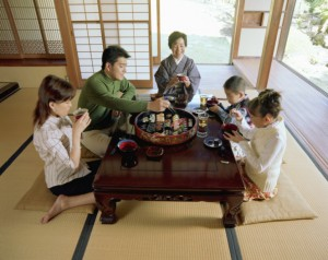 a family eating at the table and respecting Japanese tradition