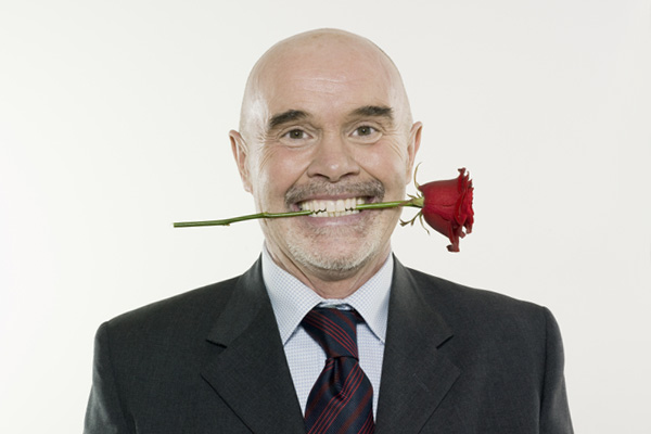 man with rose between his teeth
