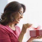 Hispanic woman opening gift