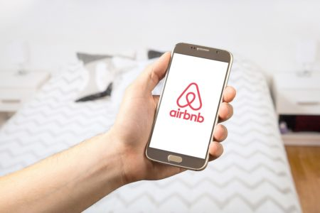 Person holding a phone with airbnb logo