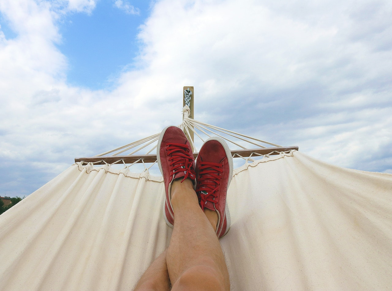 Person on a hammock with blue sky on the background